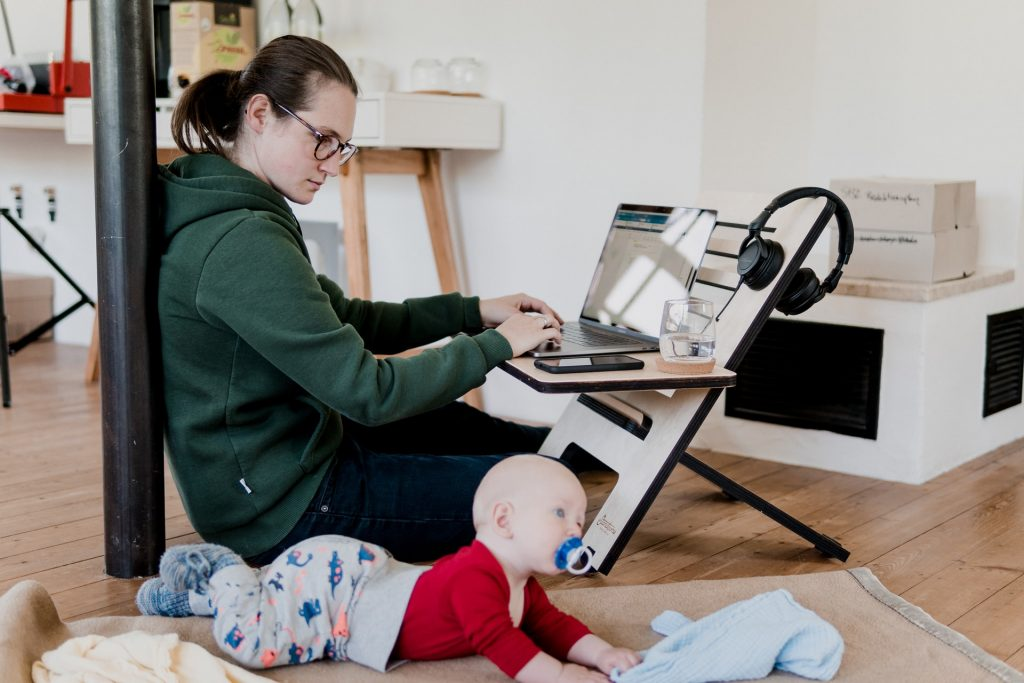 mother working from home - at flexible and height-adjustable desk with baby