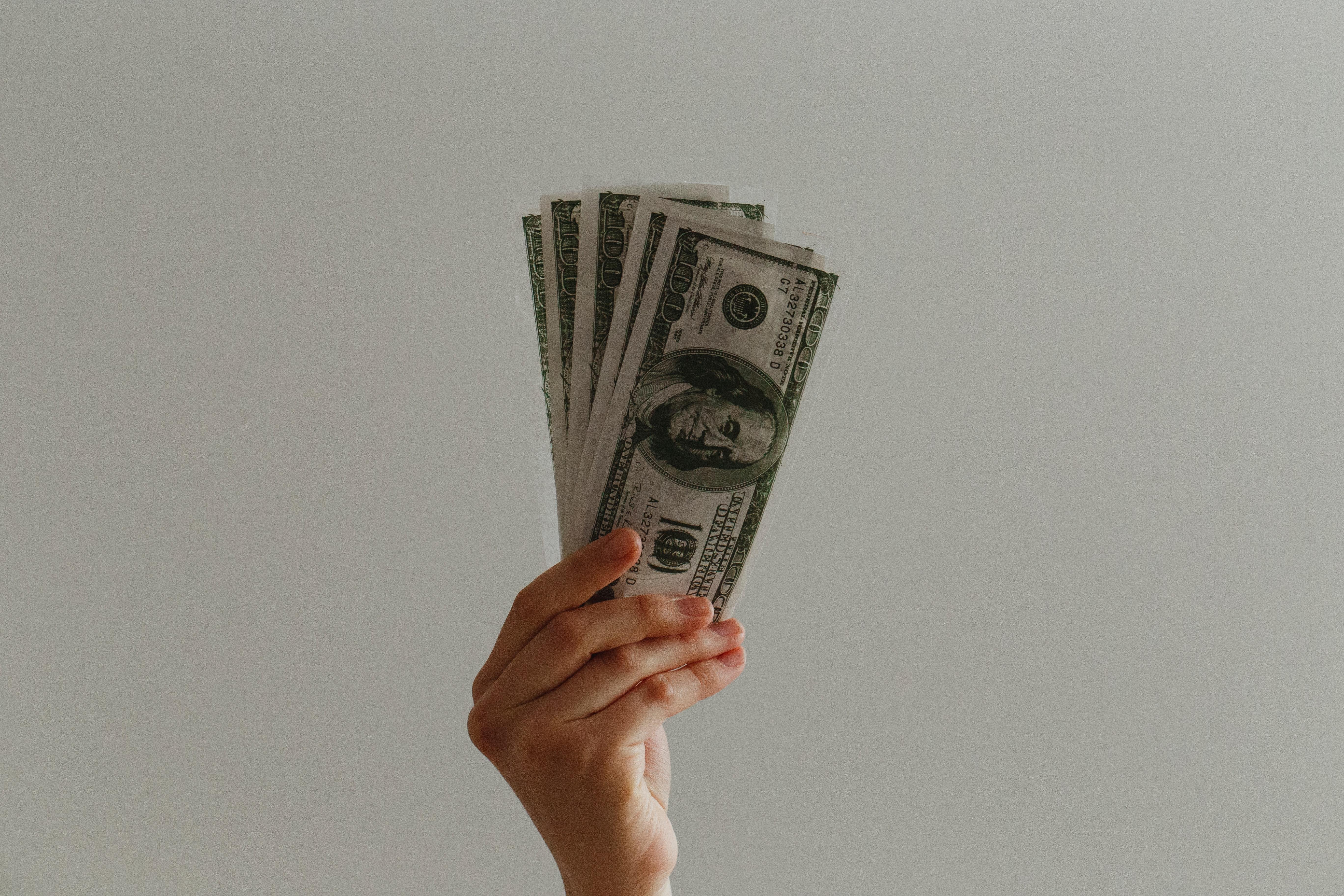 Man in work attire holding cash